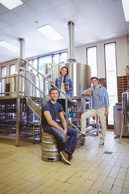 Man siting on keg and his colleague holding a glass of beer in the factory